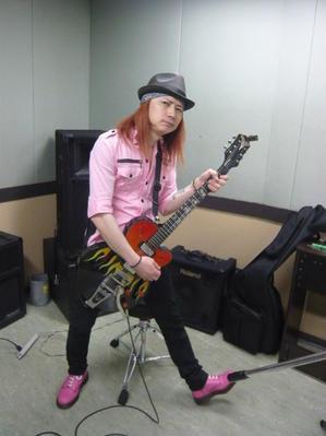 ギターを担いだピンクおっさん - 69ROCK YOU ロックユー