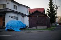 黄昏の車庫と梱包された車 - inside out