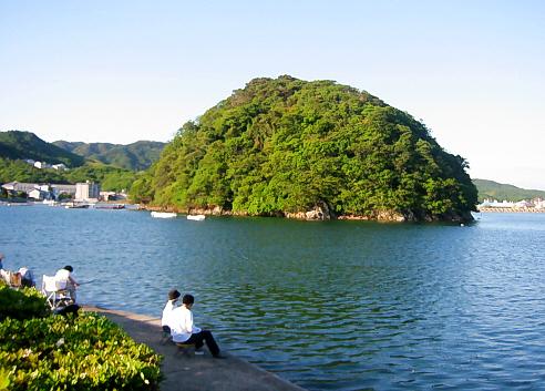 穏やかな入り江の海。青い海面にぽっかり浮かぶ丸い小さな緑の島、岸辺ではカップルや家族連れが釣り糸を垂れていて、ゆったりとした時間が流れているようです。
