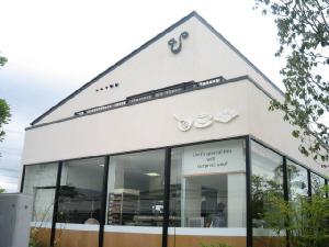 ケーキ屋さんに併設してあるカフェの写真。白い三角屋根の建物、広く窓がとってあります