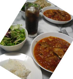 丸い白いお皿に入れられたチキンの煮込み料理。ライスとサラダも並べられています。真ん中にグラスに注がれたコーラが