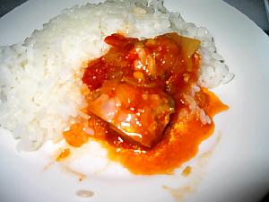 ライスの横に鶏肉の料理を乗っけて、ご飯と一緒に食べている様子。ソースの赤っぽい色がスパイシーさを物語っています