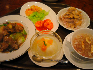 手前真ん中に、ゼリーのような白いデザートボウル。その左に牛肉と青い葉が覗くあんかけご飯。右側にはスープ。向こう側に、エビの盛り合わせプレートと、ゴマダレのかかったお肉の小鉢が