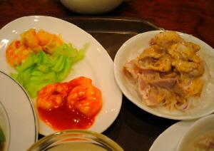 エビちりと、エビマヨの乗った、楕円形のお皿と、ゴマダレのかかったお肉、お肉の下には玉葱と大根の千切りが見えます。どちらも白い器です