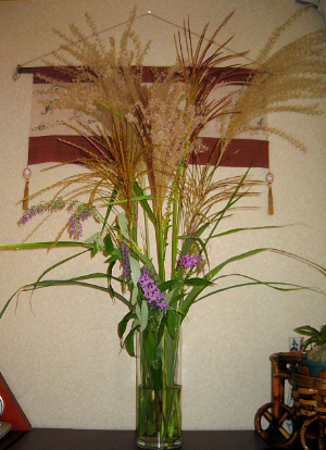 透明のガラスの花瓶に、ススキと紫色の野草の花が生けられ、茶色のチェスとの上に飾られてあります