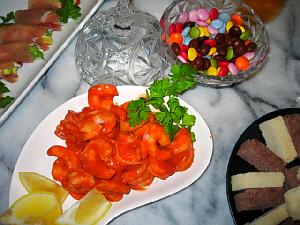ボンボン入れにマーブルチョコレート、真っ赤な色のソースが絡んだエビが変形の平たい白いお皿に、端っこには、スポンジ状のお菓子も見えます