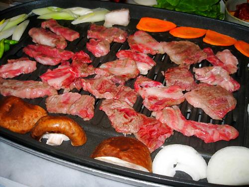 お肉用の網目のホットプレートに、半分焼色がついてきたお肉、周りに人参、しいたけ、玉葱、白ねぎ、ししとうが。