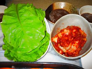 鮮やかな緑のサンチュと、真っ赤なキムチの色が綺麗。焼肉のタレの入った器も見えてます