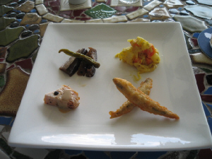 四角い白い大き目のお皿に、4種類の惣菜がバランスよく並べられています。お皿の乗ったテーブルは、モザイク柄で、色とりどりのタイルが見えます