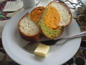 フランスパン風のパンが2切れ、丸いお皿に、小さなバターと共に盛り付けられています。バターナイフもお皿に一緒に添えられています。パンの色はオレンジ、グリーン、そして普通のパン生地の色の3色パンです