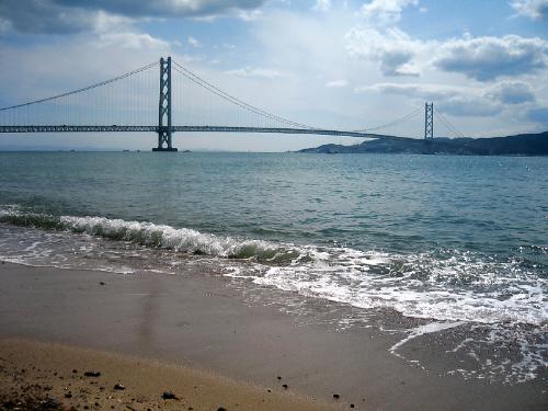 浜辺に打ち寄せる波と、その向こうに大きな橋がかかっているのが見えます。吊橋になっていて、柱がふたつくっきりと見えています。橋の向こう側に見える島は、淡路島です
