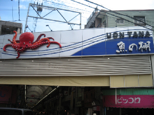 商店街のアーケードの入り口の看板。立体的なタコの姿と、魚の棚という漢字の上に、UONTANAとローマ字で書かれています。