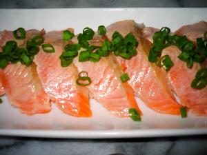 サーモンの握り寿司のアップ画像。上側に焼き色がついているのが確認されます。サーモンの色と青ネギの色のコントラストが綺麗