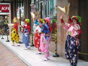 色とりどりのもんぺ姿に、巾着状の帽子、手にはすだれを持って、数人の女性が手を上のほうに掲げて躍っている姿。南京玉簾の典型的な衣装ですね