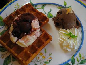華やかな白地にブルーのラインのお皿、全体にブルーの花模様が。ワッフルが2枚、その上にアイスクリームと、カカオパウダーが、その隣にはチョコレートアイスクリームと、生クリームが並んでいます