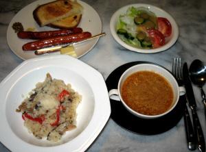 八角形の白い深型のお皿にリゾットが、その右隣に黒いお皿の上に白いスープカップ。向こう側に丸い平たいお皿にパンと、チョリソが2本、小さなバターとバターナイフも一緒にお皿に乗せられてます。その右側に小さなサラダボールが並んでいます
