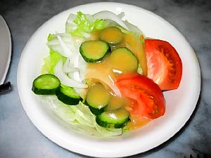 白いやや小さめのボウルに、野菜ととろっとした濃い目の黄色いドレッシングがかかっています