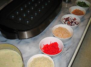 テーブルの上に、大きなホットプレート、そしてその周りに、紅生姜、桜えび、タコ、揚げ玉、青ネギ、削り節、たこ焼きの生地が並んでいます。