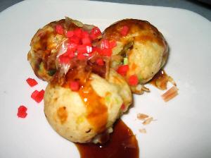 白いお皿に、丸まるのたこ焼きが3つ。ソースがかかって、紅しょうがもちらほらかかっています。削り節も見えてます