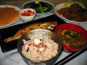 ちょっと斜めから撮った写真。ご飯、味噌汁が手前側、向こうに焼き魚、更にその奥に、玉子焼き、キムチ、ナスの焼き物、一番奥に生姜焼きが見えます。