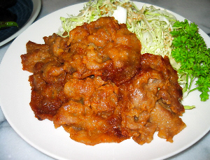 同じ白い平たい丸皿に、キャベツの千切りにドレッシング、キツネ色にこんがり焼けた、薄いお肉が綺麗に並べられています。緑のパセリがアクセントに。