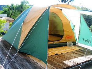 高床式に作られた木の土台の上に、テントが張られている様子。テントの色は、グリーンとベージュの2色の。そして組み立てられたテントの中には、エアマットが見えます。