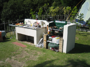 炊事場と、レンガが積み上げられたグリル炉が並んでいます。流し台にはキッチン用品が並べられていて、隣のグリル炉には、アウトドア用のコンロが設置されています。その下にはお鍋や小道具類が見えます。