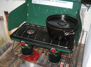 簡易式の2バーナーのガスコンロ。ボンベ缶を取り付けて使用します。コンパクトですが、自動点火の優れものです。コンロの上にはダッチオーブンが乗せられて、準備万端な様子です。
