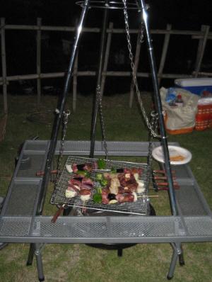三角錐型の炭火コンロ。上から鎖が下がっていて、その先端に鍋とかをぶら下げて煮炊きできる、田舎の囲炉裏端の雰囲気が味わえます。その三角の足回りに、四角い囲いがしてあります。まるで本当の囲炉裏端の雰囲気が。三点から鎖で四角い網が吊り下げられて、その網の上には串に刺したお肉やら野菜が乗ってます。