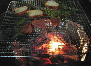 網の上に枝豆とハム、そしてフランスパンの薄切りが炙られています。火の灯りが幻想的です。焚き火の雰囲気は、やっぱりキャンプには不可欠ですね。