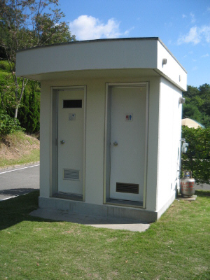 トイレとシャワールームの二つのドアが見える小さなコンクリート作りの棟。各区画に一個ずつ設置されています。勿論これのない区画もあります。