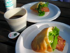 白い紙皿に乗ったピタパン。顔を覗かせているのは、レタスと焼いた厚いハム。コーヒーとミルク、飲むヨーグルトも添えられています。