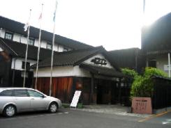 白壁に黒い屋根の、お醤油記念館の入り口風景です。蔵のような建物が後ろ側に見えています。