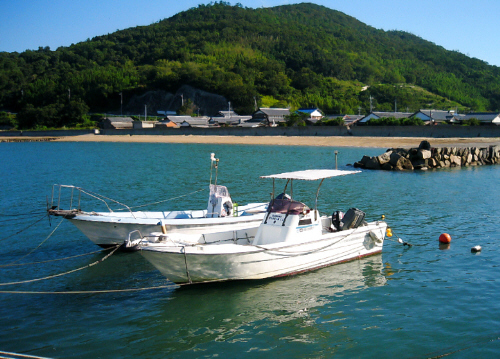 突堤に係留されている二艘のボート。穏やかな綺麗な海にその姿を映しています。向こう側が岸辺のようで、小さなビーチが見えます。ビーチのその向こうには小高い丘が見え、まるで絵葉書の中のようです。