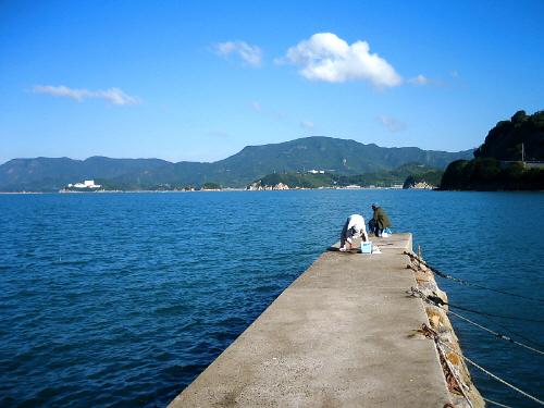 紺碧の海に突き出した突堤。地元の方でしょうおじさんが二人釣竿を出しています。一人の方は、今釣れたようで、魚から針を外す作業をしているようです。海の向こうには山間が広がって、のどかな海の風景です。
