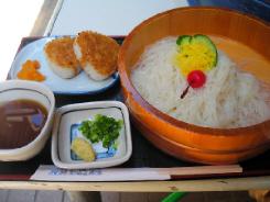 大き目の桶に入った素麺。彩りにきゅうりとさくらんぼ、千切り玉子焼きが一緒に。その左隣に焼きおにぎりが二個と、素麺の漬け汁、薬味が添えられています。