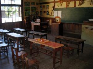 いかにも昔懐かしい教室という風景。木の二人用のくっついた机に、木の椅子。古い黒板の上側に木の三角定規などが吊るしてあります。教壇も端っこの先生の机も黒光りした木製です。窓も木枠でガラスも昔風のガラスが。
