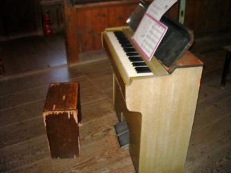 ピアノではなく、オルガン。椅子も古ぼけた箱型の椅子が置かれています。扉が開けてあって譜面が乗せられています
