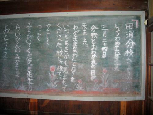教室の前の端にかけてあった黒板。中には・・・田浦分校さようなら<br /> しょうわ四十六年三月二十四日・分校とおわかれの日が来ました。わがままなわたしたちを、いつもあたたかく見まもってくださった校しゃ校てい、やさしく、つよく、みちびいてくれた先生方、らいひんのみなさま、おとうさん、おかあさん、ありがとうございました。と書かれています。