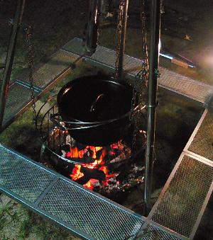 囲炉裏端の風景です。燃える炭火の上に釣りされられた網、その上に黒光りしたダッチオーブンが。さてさて中味は?