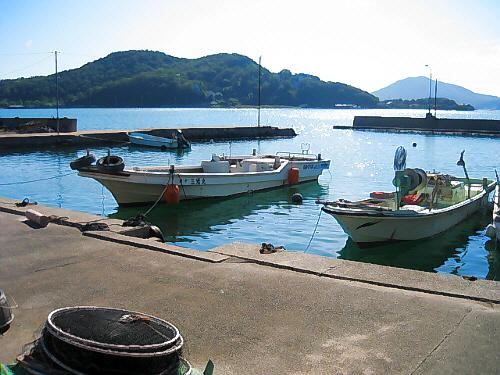 小さな港の風景。道路のすぐ脇に港が隣接しています。小さな漁船が何艘が係留されています。入り江の向こうには、岬の先端が。キラキラ水面が光って海というよりは湖のようです。
