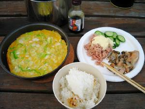 木のテーブルの上に並んでいるのは、鍋ごとの玉子焼き、白いご飯、そして白いお皿に、きゅうりとツナのサラダ、その端っこにはらすの焼いたものが。
