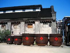 白壁の前にずらっと並んだ醤油ダル。木目の大きな樽にもやはり丸の中に金の文字が赤く入れられています。