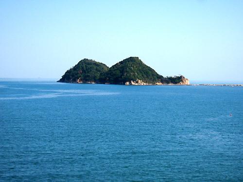 海に浮かんだ小島。桟橋状のもので繋がっているようです。ここも潮の満ち引きで通れなくなるのかも知れません。真っ青な海にぽこっと浮かんだ緑の島、その向こうに広がる空の青。雲ひとつなくまるで絵に描いたような風景です。