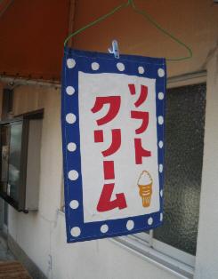 白地に青に白の水玉の縁取り、赤い文字でソフトクリームと書かれた垂れ幕。こちらは小さなソフトクリームの絵も描かれています。