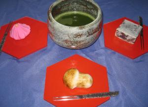 ブルーのクロスに、赤い木製の銘々皿が3つ、その上に和菓子が乗せられて、真ん中に抹茶茶碗が置いてあります。
