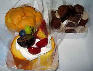 ケーキが3つ。ひとつはシュークリーム、ひとつはスポンジ台に乗ったクリームと果物がたっぷり、そしてもうひとつは、チョコ色のスポンジの角切りと生クリームがひとつに纏まっています。