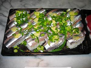 スチロール容器に入ったままのさんまの握り寿司、上には青ネギと生姜のすり卸がトッピングされています。