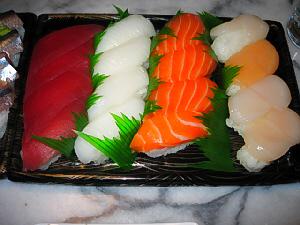 こちらも容器に入ったままの握り寿司、マグロ、イカ、サーモン、ほたてが並んでいます。