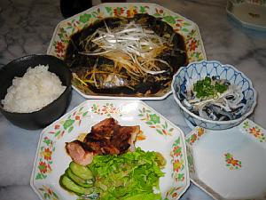 手前にチキンのグリルが3切れ、レタスの千切りときゅうりが添えられています。白いご飯と、大皿には魚の料理が見えます。小ぶりの鉢にとらふぐの皮が盛られていて、上には青ネギが散らしてあります。